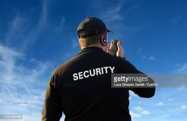 rear view of security guard talking on walkie-talkie - watchmen stock pictures, royalty-free photos & images