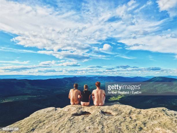 rear view of semi dressed women with naked men sitting on cliff against sky - bare bottom stock pictures, royalty-free photos & images