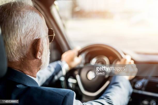 rear view of senior businessman driving a car to work. - car insurance stock pictures, royalty-free photos & images