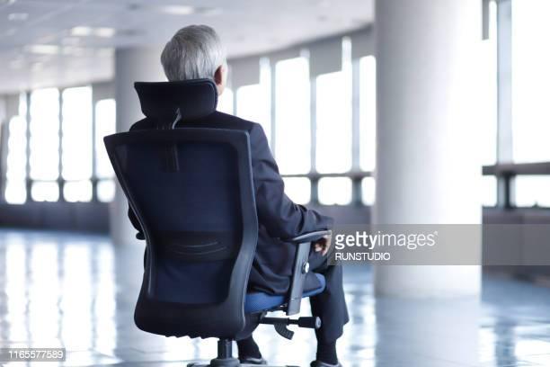 rear view of senior businessman sitting on chair in office - bestuursvoorzitter stockfoto's en -beelden