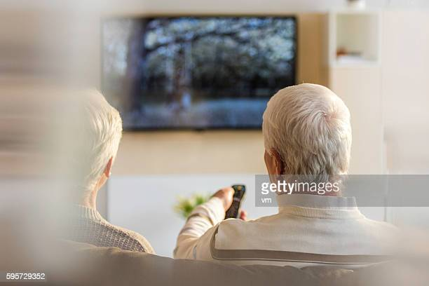 Rear view of senior couple looking television