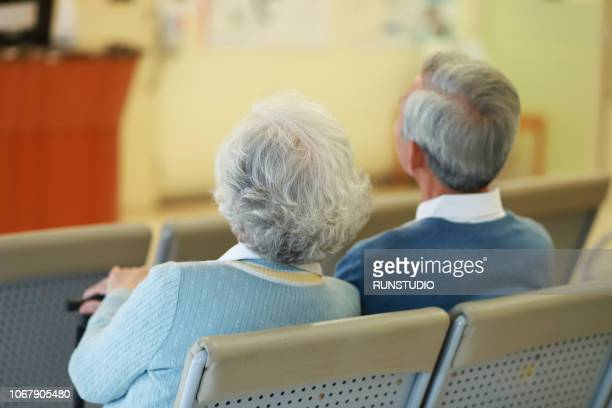Rear view of senior couple sitting in waiting room in hospital