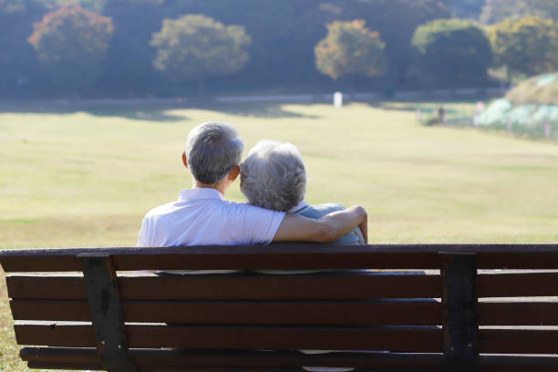 rear view of senior couple sitting on park bench - asian old couple in the park stock pictures, royalty-free photos & images