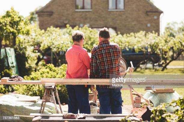 Rear view of senior couple standing by wooden plank against house at yard