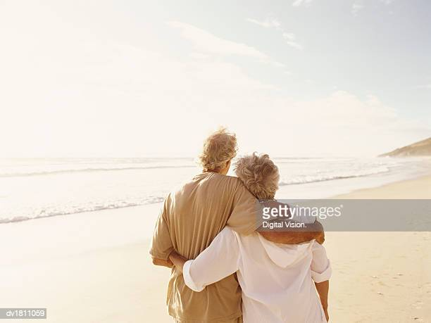 rear view of senior couple standing on a beach with their arms around each other - overexposed stock pictures, royalty-free photos & images
