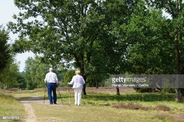 Rear View Of Senior Couple Walking On Grassy Field At Park