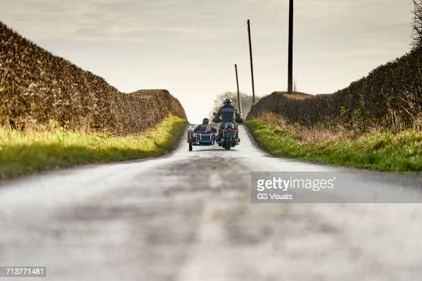 Rear view of senior man and grandson riding motorcycle and sidecar on rural road
