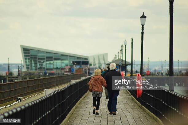 rear view of senior man and woman walking on bridge against sky - southend on sea stock pictures, royalty-free photos & images
