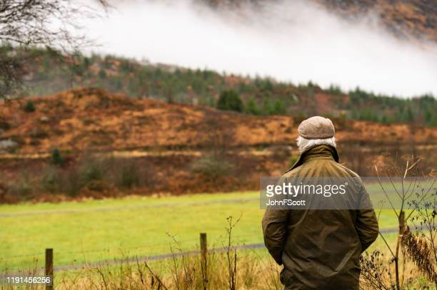 rear view of senior man in rural south west scotland - galloway scotland stock pictures, royalty-free photos & images