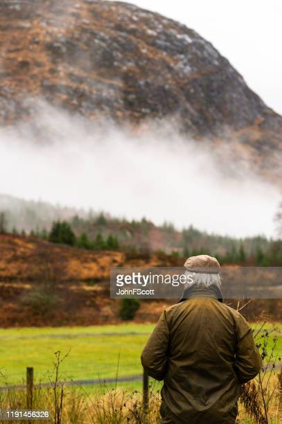 rear view of senior man in rural south west scotland - johnfscott stock pictures, royalty-free photos & images