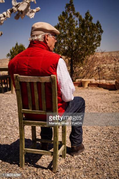 rear view of senior man looking away while sitting on chair outdoors - mariana abad fotografías e imágenes de stock