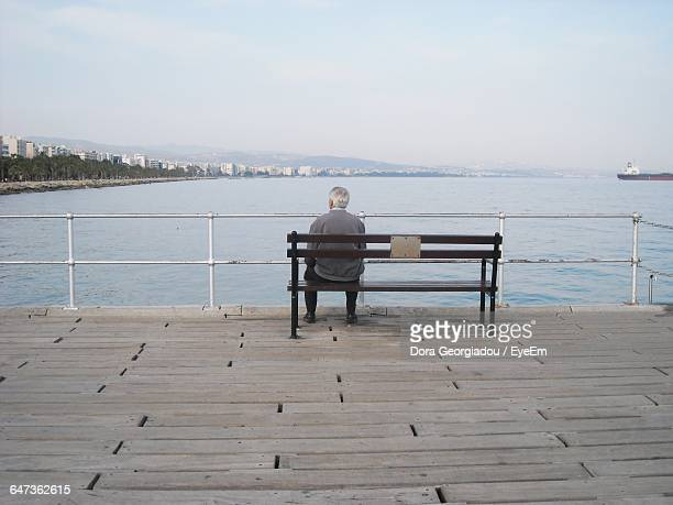 Rear View Of Senior Man Sitting On Bench Against Sky