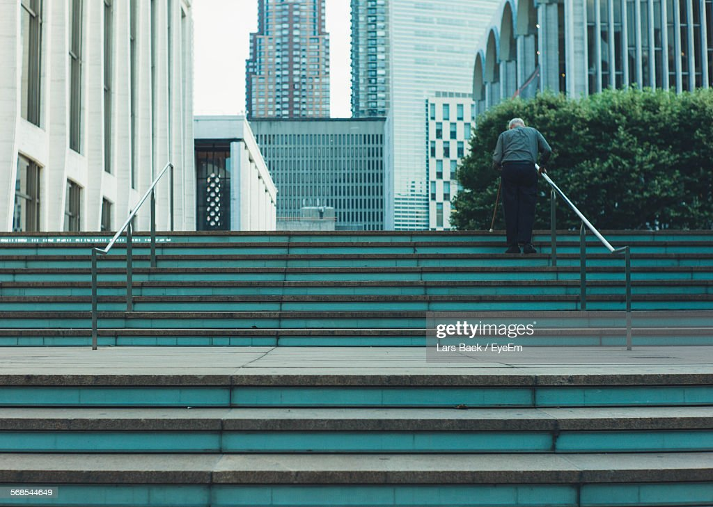 Rear View Of Senior Man Walking On Lincoln Center For The Performing Arts Staircase : Stock Photo