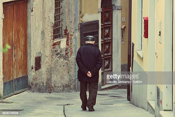 rear view of senior man walking on street amidst buildings - hands behind back stock pictures, royalty-free photos & images