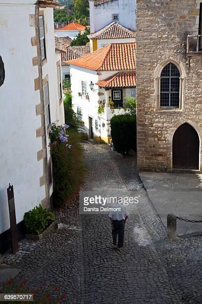 rear view of senior man walking through old town, obidos, portugal - leiria district stock photos and pictures