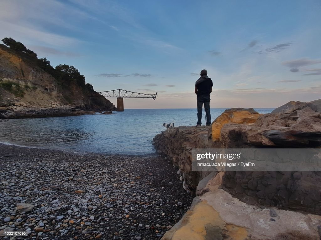 rear view of senior man with dog standing on rocks by sea against