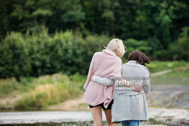 a rear view of senior mother and adult daughter walking arm in arm by the water reservoir in nature. - length stock pictures, royalty-free photos & images