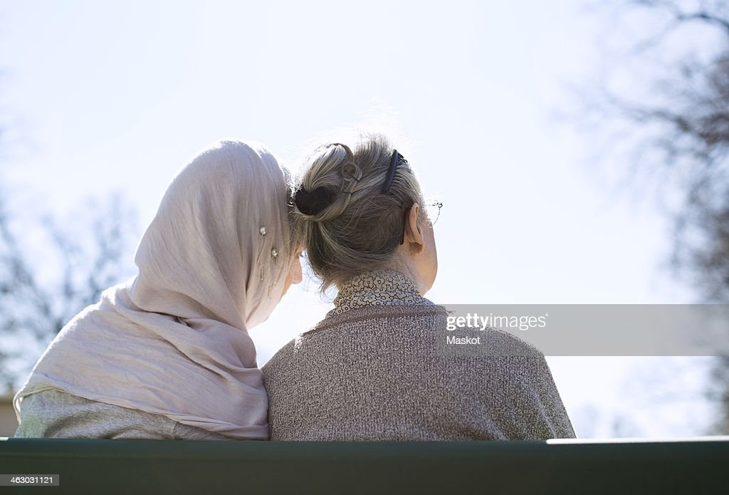 Rear view of senior woman and female home caregiver sitting together on park bench : Stock Photo