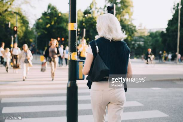 rear view of senior woman crossing road in city - focus on foreground stock pictures, royalty-free photos & images