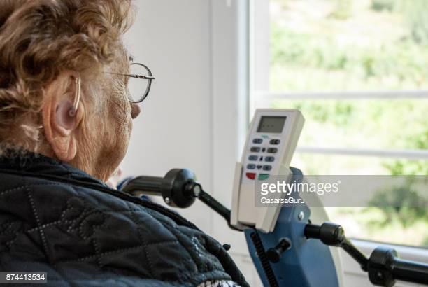 Rear View Of Senior Woman Exercising On Exercise Bike