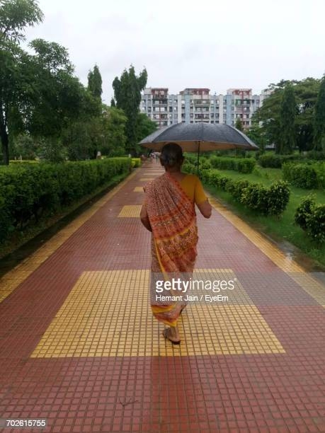 Rear View Of Senior Woman Holding Umbrella While Walking On Footpath In Garden During Rainy Season