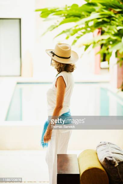 rear view of senior woman looking out on spa pool and garden - three quarter length stock pictures, royalty-free photos & images
