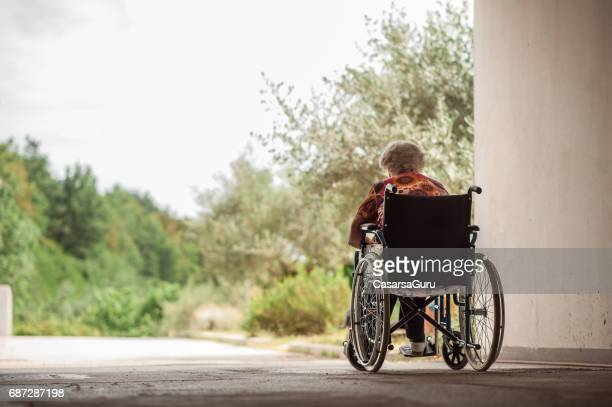 rear view of senior woman on wheelchair in the garage corridor - vulnerability stock photos and pictures