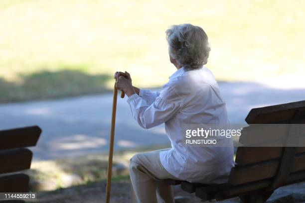 rear view of senior woman sitting on park bench - loneliness stock pictures, royalty-free photos & images