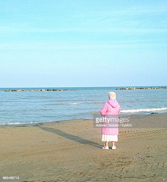 Rear View Of Senior Woman Standing At Beach Against Sky
