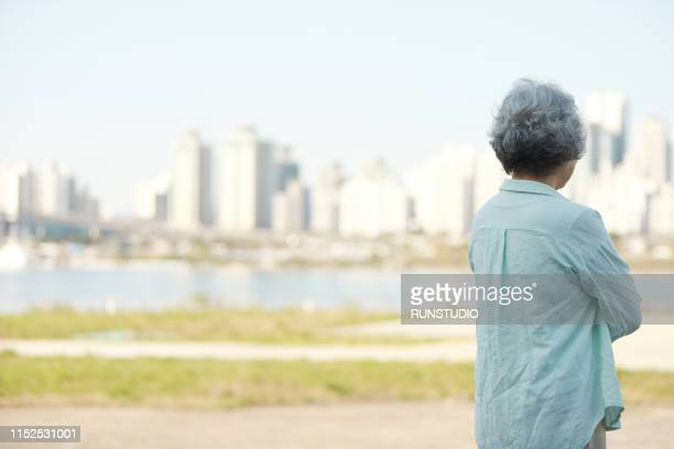 rear view of senior woman standing by river bank - riverbank stock pictures, royalty-free photos & images