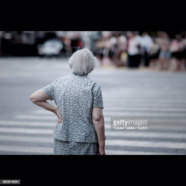 rear view of senior woman standing with hand on hip at zebra crossing - pedestrian crossing stock photos and pictures
