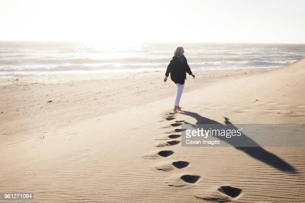 rear view of senior woman walking on sand at beach against clear sky during sunny day - solo una donna anziana foto e immagini stock