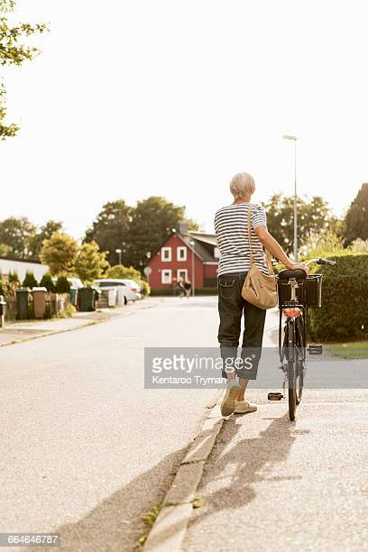 Rear view of senior woman walking with bicycle on sidewalk against clear sky