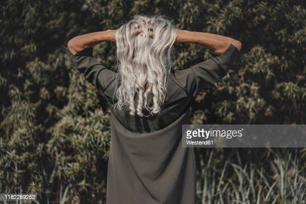 rear view of senior woman with hands in her white hair - hand in hair stock pictures, royalty-free photos & images