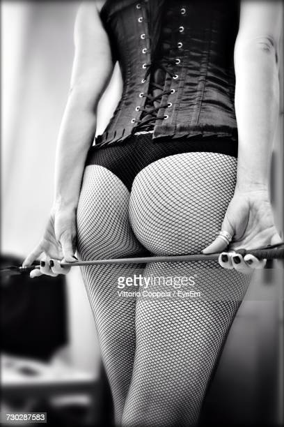 rear view of sensuous woman holding cane under buttocks - corset stock pictures, royalty-free photos & images