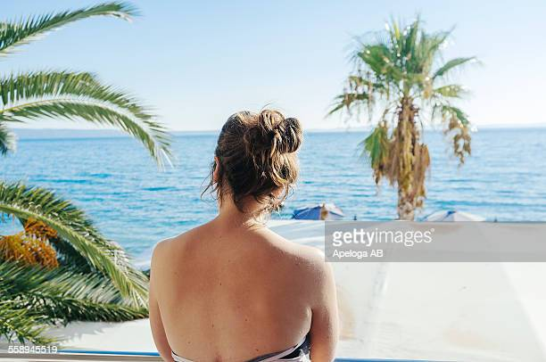 Rear view of sensuous woman looking at sea through window
