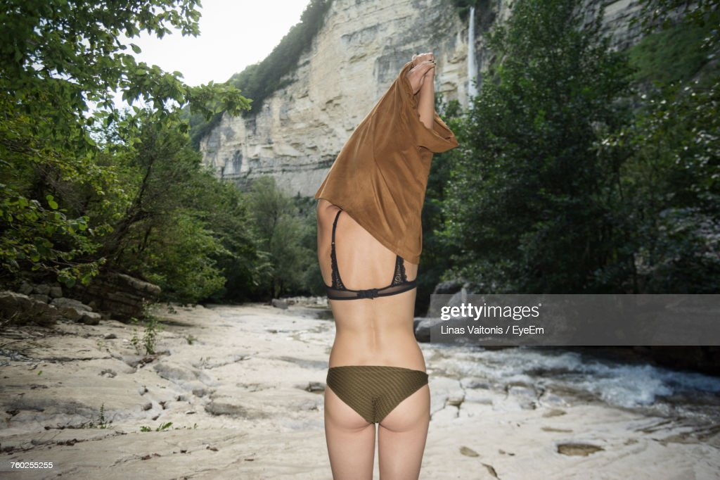 Rear View Of Sensuous Woman Pulling T-Shirt While Standing Against Trees At Forest : Stock Photo