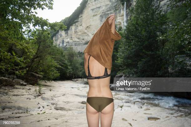 Rear View Of Sensuous Woman Pulling T-Shirt While Standing Against Trees At Forest