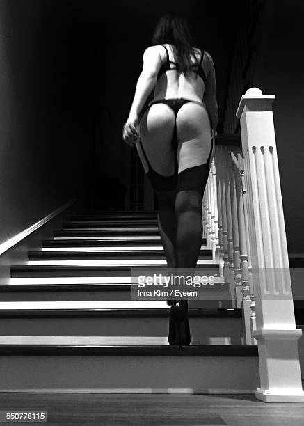 Rear View Of Sensuous Young Woman In Lingerie And Stockings Moving Up Stairs