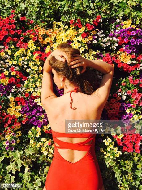 Rear View Of Sensuous Young Woman Standing Against Flowers At Park