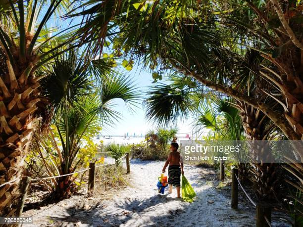 Rear View Of Shirtless Boy Walking With Toys And Towel Amidst Palm Trees At Beach