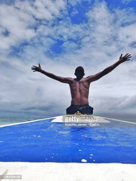 rear view of shirtless man in swimming pool against sky - mombasa stock pictures, royalty-free photos & images