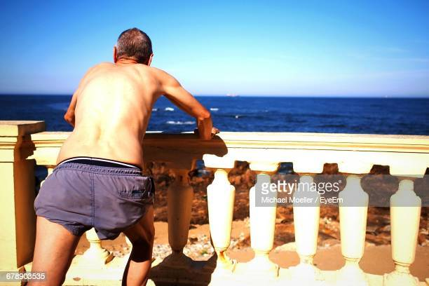 Rear View Of Shirtless Man Leaning On Railing Against Sky