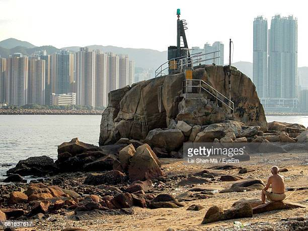 rear view of shirtless man sitting on rock at beach in city during sunny day - my lai sit fotografías e imágenes de stock