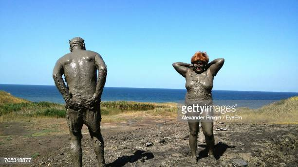 rear view of shirtless man standing by sea against clear blue sky - freaky couples stockfoto's en -beelden