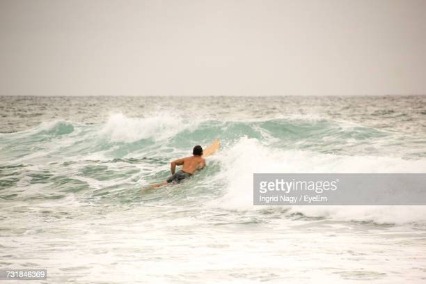 Rear View Of Shirtless Man Surfing In Sea Against Sky