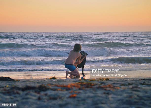 Rear View Of Shirtless Teenage Boy With Dog At Beach During Sunset