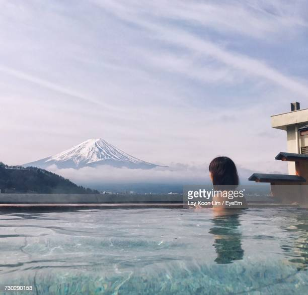 Rear View Of Shirtless Woman In Hot Spring Against Snowcapped Mt Fuji