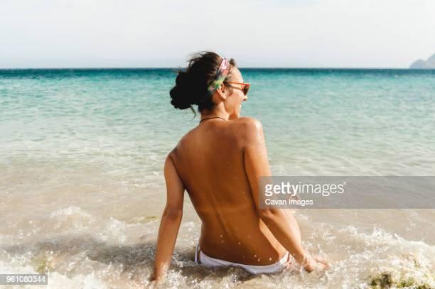rear view of shirtless woman sunbathing at beach - ontbloot bovenlichaam stockfoto's en -beelden