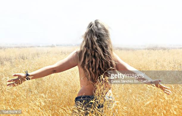 rear view of shirtless woman with arms outstretched standing on field - oben ohne frau stock-fotos und bilder